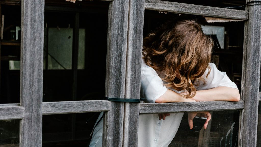 A woman leans out a St. Louis window looking for answers to her health problems – find answers in Michelle Marie keynote talks.